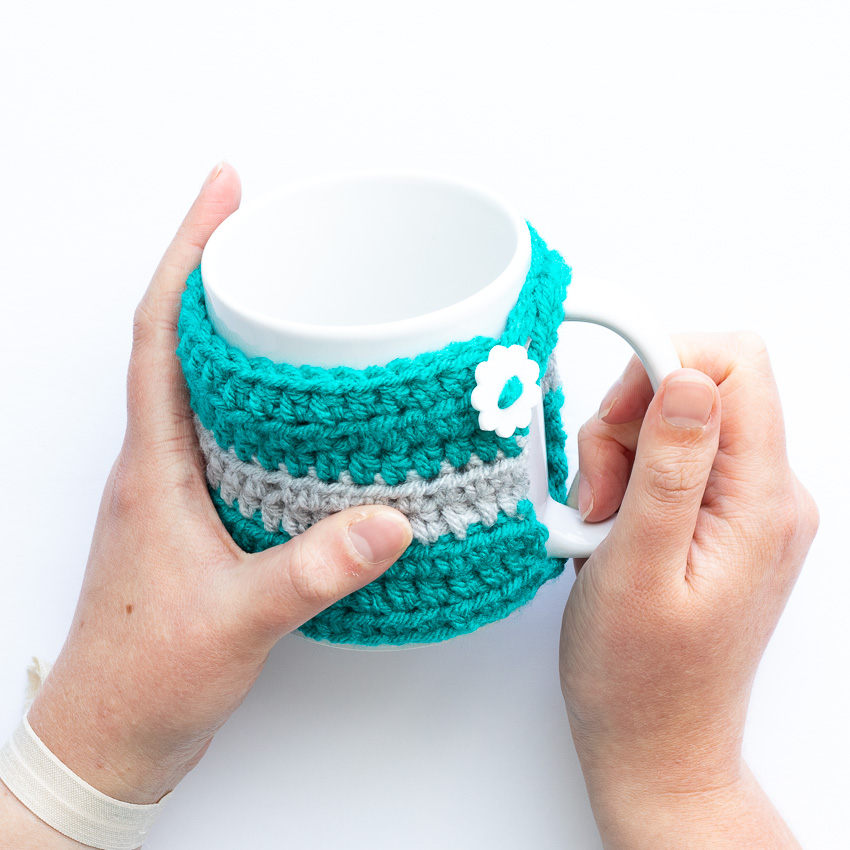 two hands holding a white mug with a teal and grey crocheted striped mug cozy