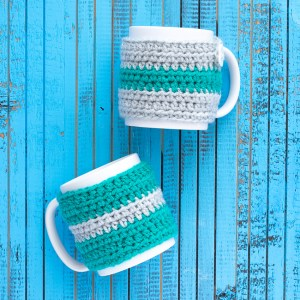 two white mugs with crocheted striped mug cozies on a blue wooden background