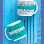 """two mugs on a blue wooden background with text overlay """"beginner striped mug cozy - you should craft"""""""