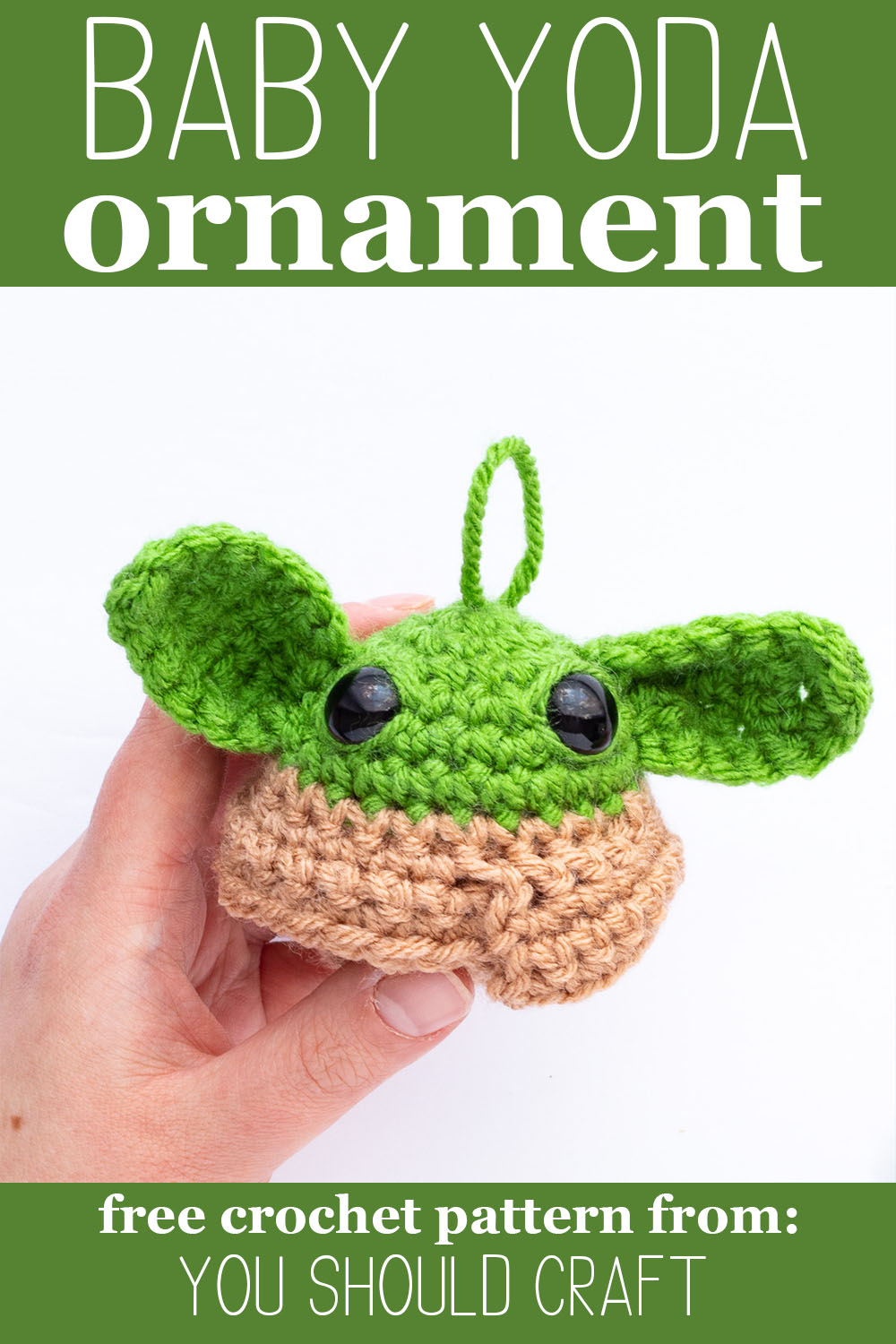 "hand holding a crocheted grogu ornament with text ""baby yoda ornament - free crochet pattern by you should craft"""