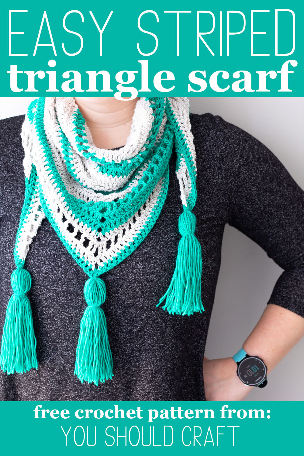 woman in a dark grey dress with a teal and grey striped triangle scarf crocheted, with tassels