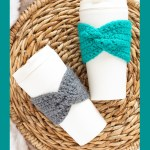 two coffee cups with crocheted cup cozies on a woven placemat with text overlay: easy twisted cup cozy - you should craft