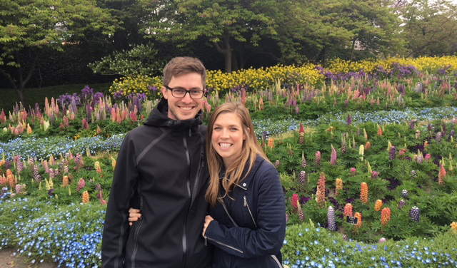 Megan Deutschman with husband smiling in a flower garden