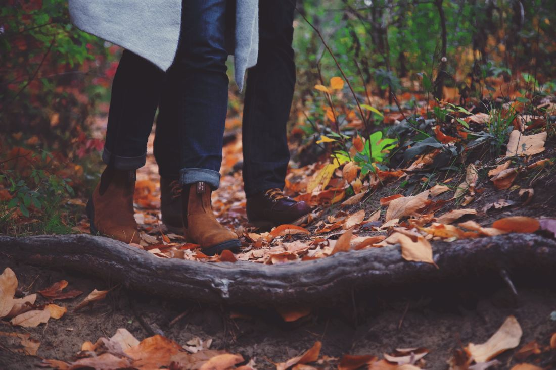 Shot of two people wearing boots on a trail in the forest