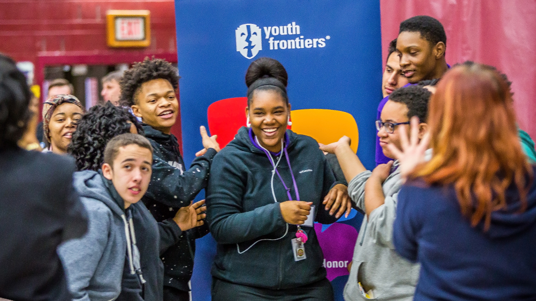 YFLC Group of students laughing together in front of a youth frontiers banner
