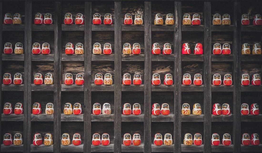 A shelf grid of many Russian nesting dolls