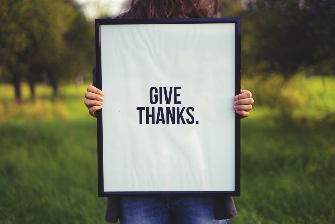 a person holding up a sign that says give thanks