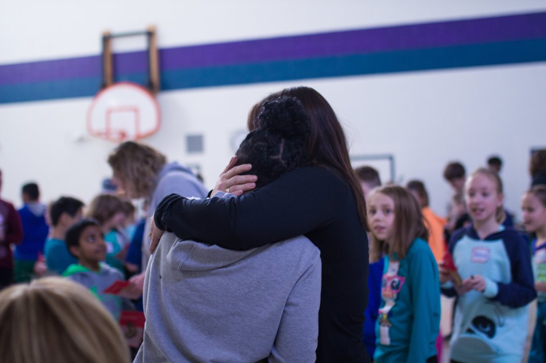 Moved by a Youth Frontiers Retreat, an educator hugs a colleague