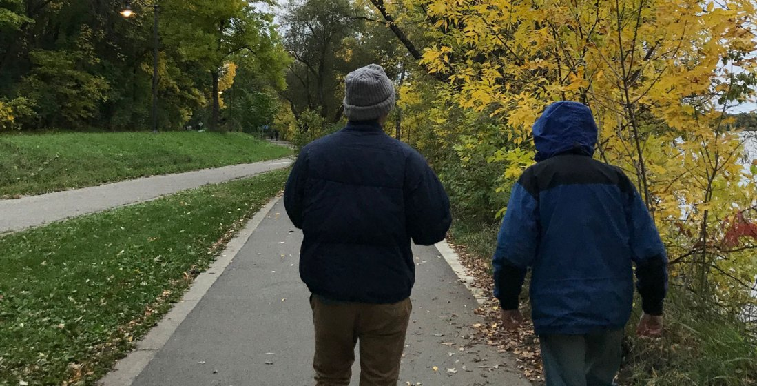 Family walking on a tree-lined path in fall.