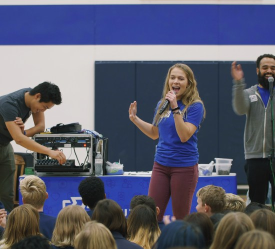 Ally Baker singing on the mic in front of a croud of kids at a Youth Frontiers retreat.