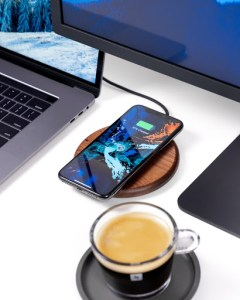 table with iphone on a wireless charger and coffee mug