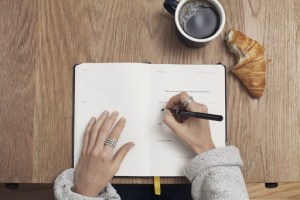 person with pen writing, coffee on table