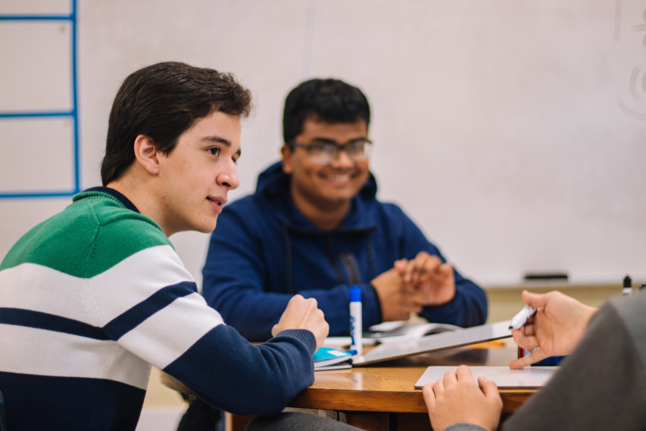 11Two young male teens, sitting at a desk smiling and looking at a third person not pictured