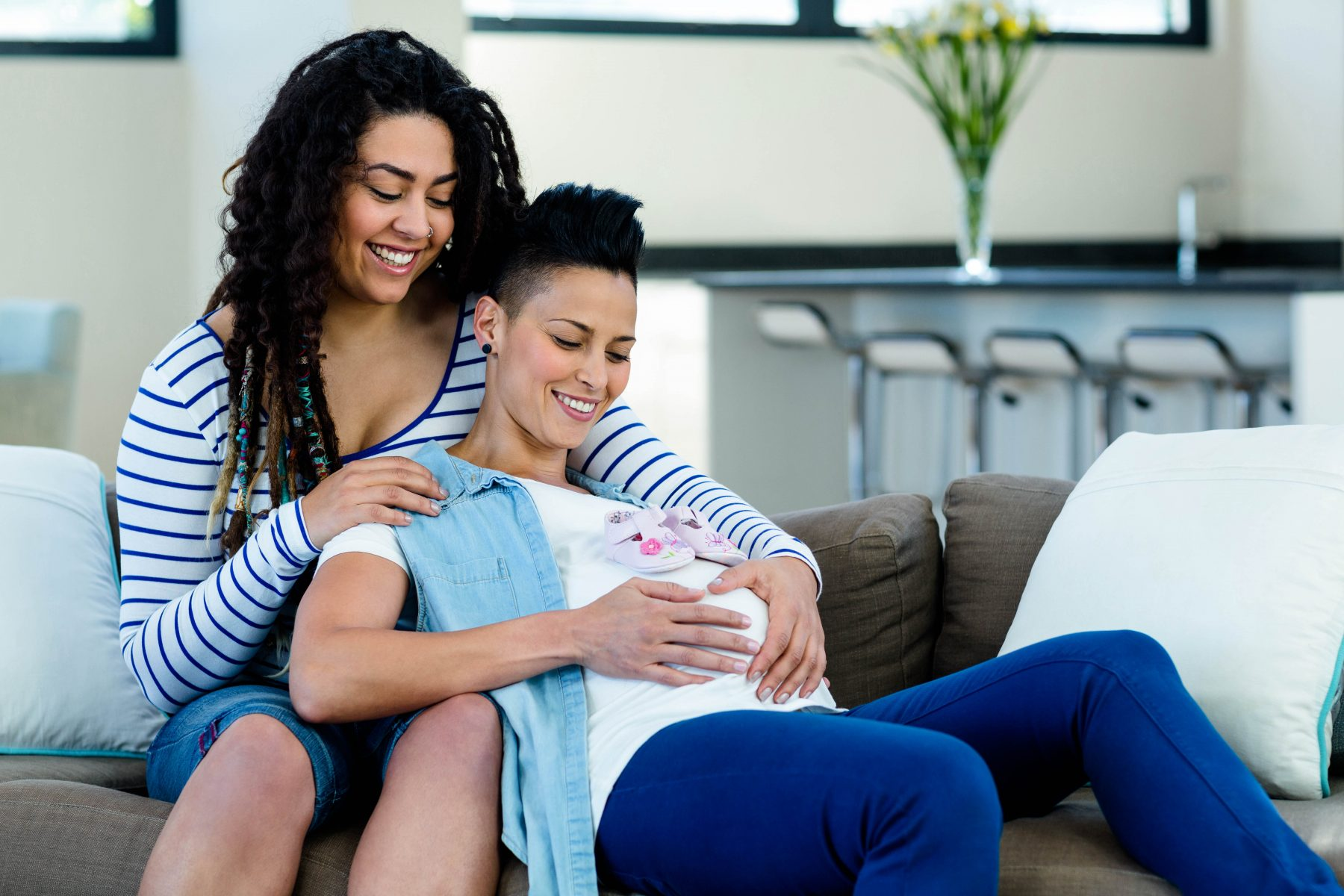 Pregnant lesbian couple sitting on sofa with a pair of pink baby shoes