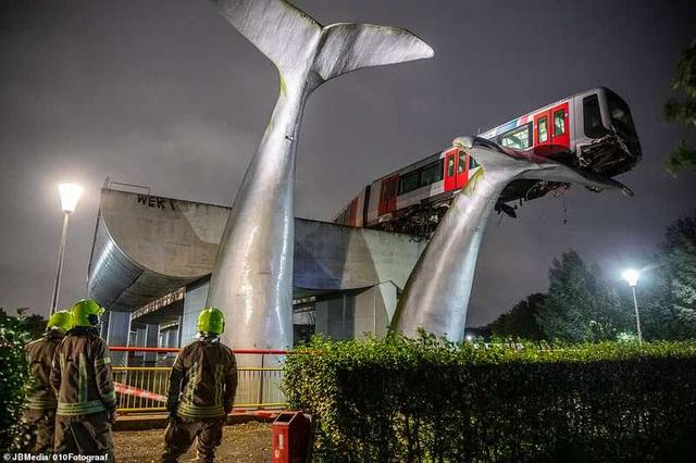 """The Dutch subway train hits through the guardrail and the carriage hangs in the air and is""""lifted"""" by a whale sculpture"""