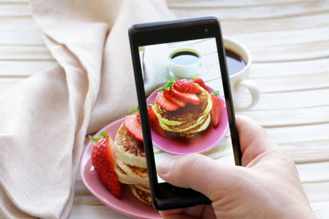 person-taking-picture-of-breakfast-with-smartphone
