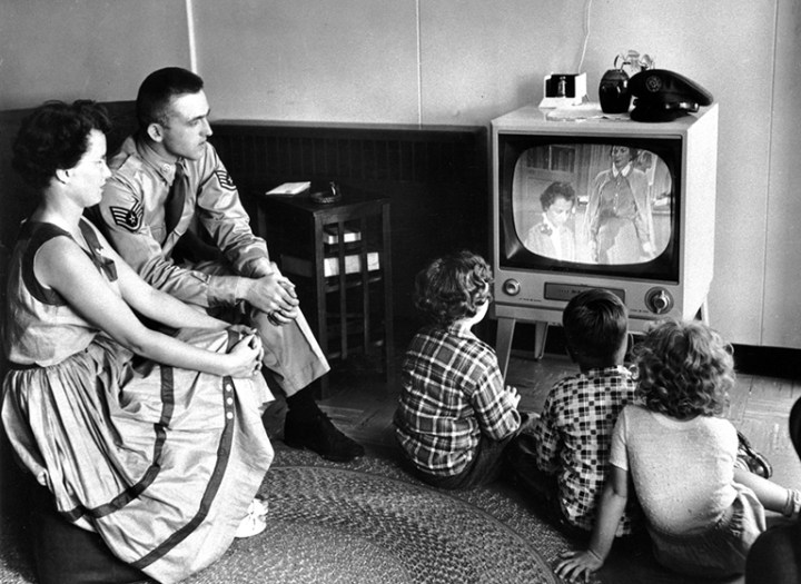 A United States serviceman views television with his family at the U.S. Limestone, Maine, base on July 1, 1954. Nearly every household in the United States has at least one televison set and viewers have their sets on an average of seven hours daily.  Television, the tool of mass communications, gave birth to cable television, encompassing time and thought as no other cultural phenomenon ever has.   (AP Photo)