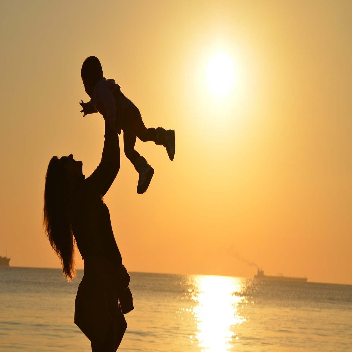 woman holding a baby on the beach at the dusk