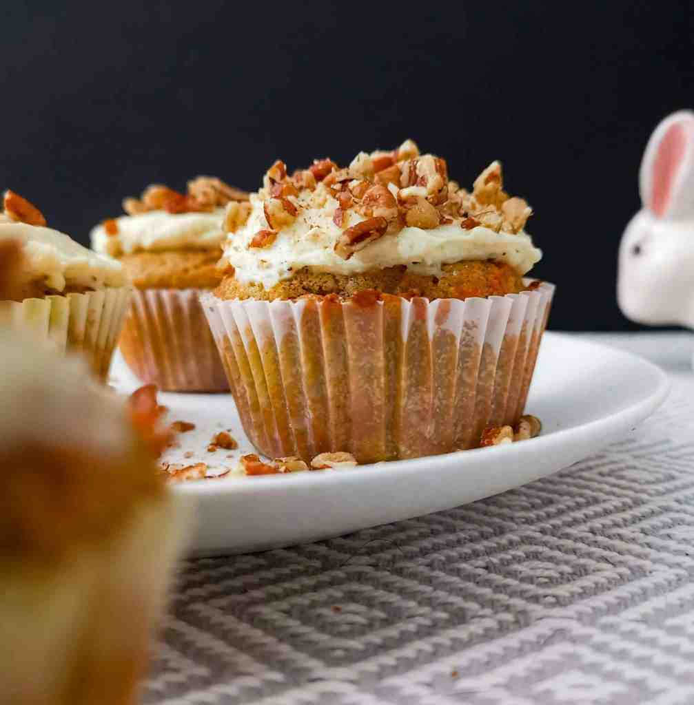 Low carb carrot cupcake on a plat with an Easter bunny in the background