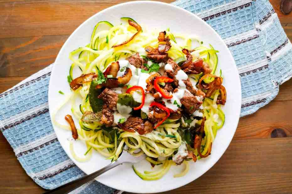 Low Carb Philly Cheesesteak Zoodles topped with onions and hot peppers
