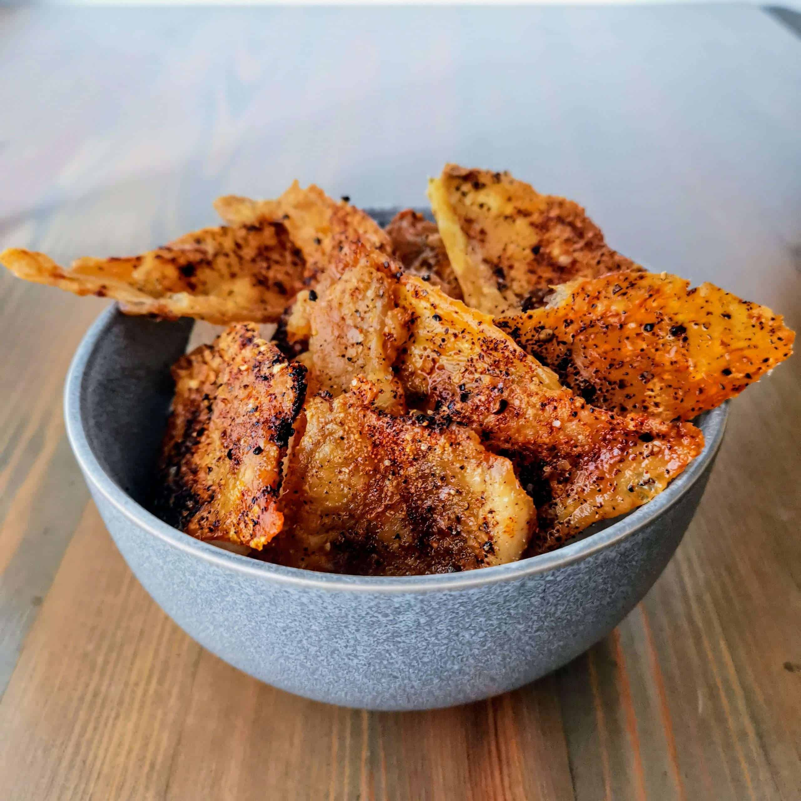 Keto friendly chicken skin nacho chips in a bowl from an angle