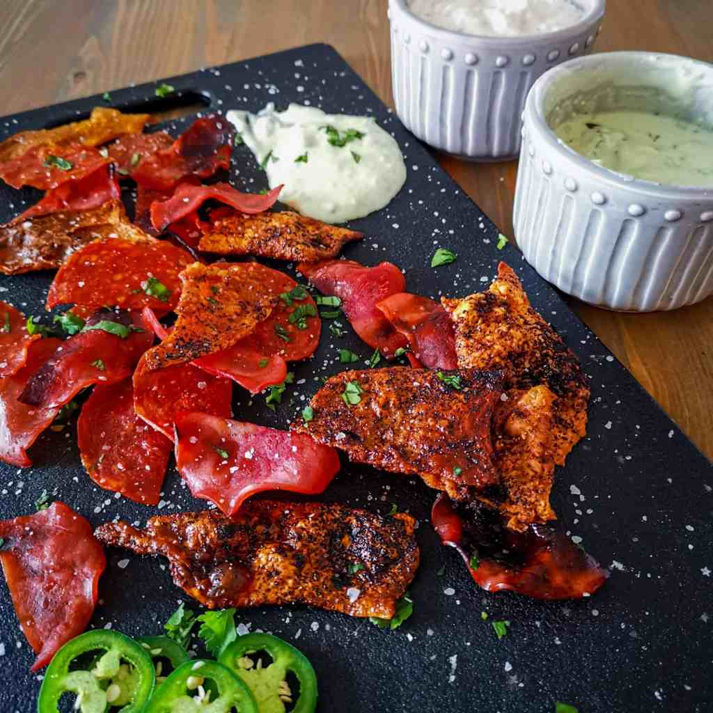 A variety of homemade low carb keto friendly meat chips on a platter with dip