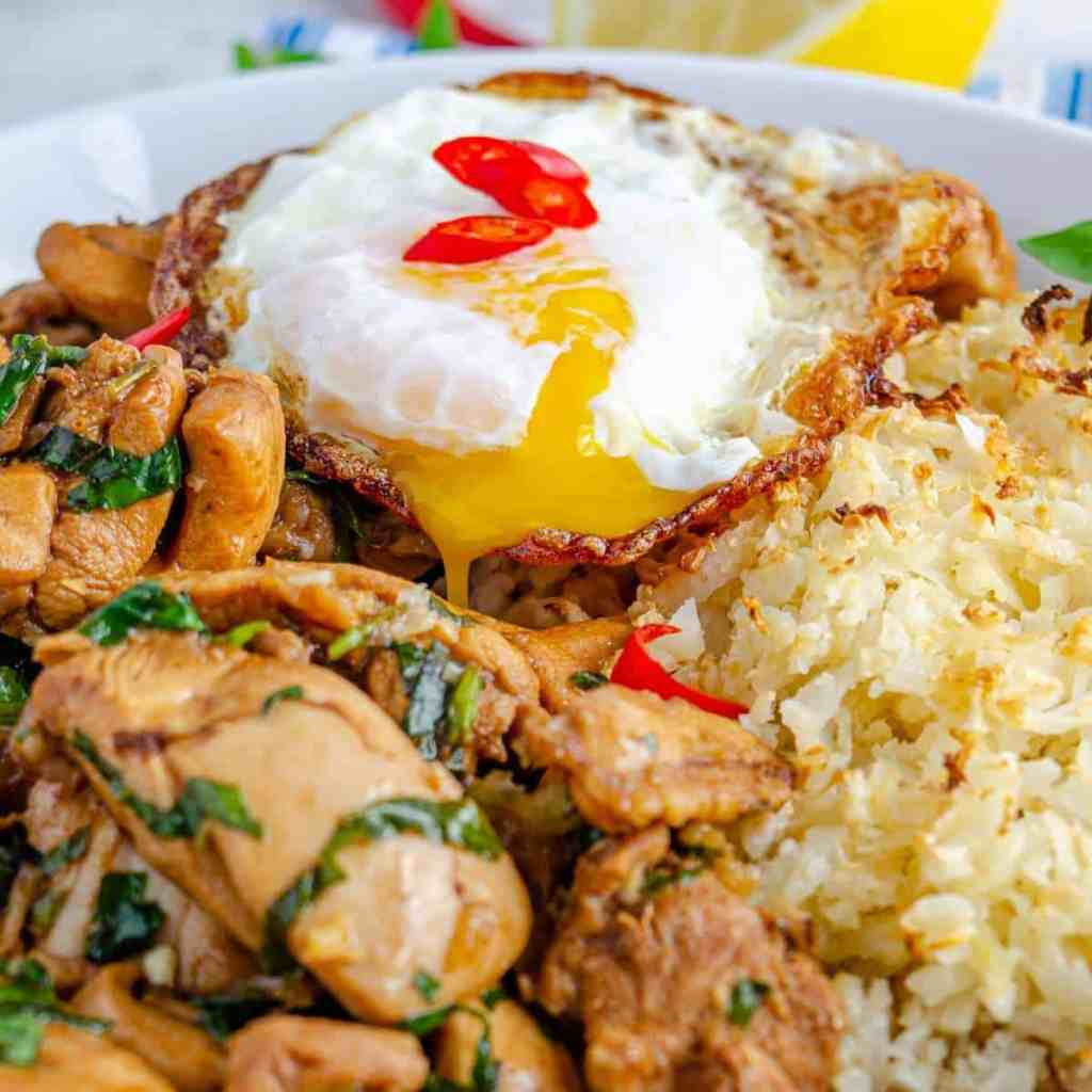 A crispy oozing fried egg over top Thai basil chicken