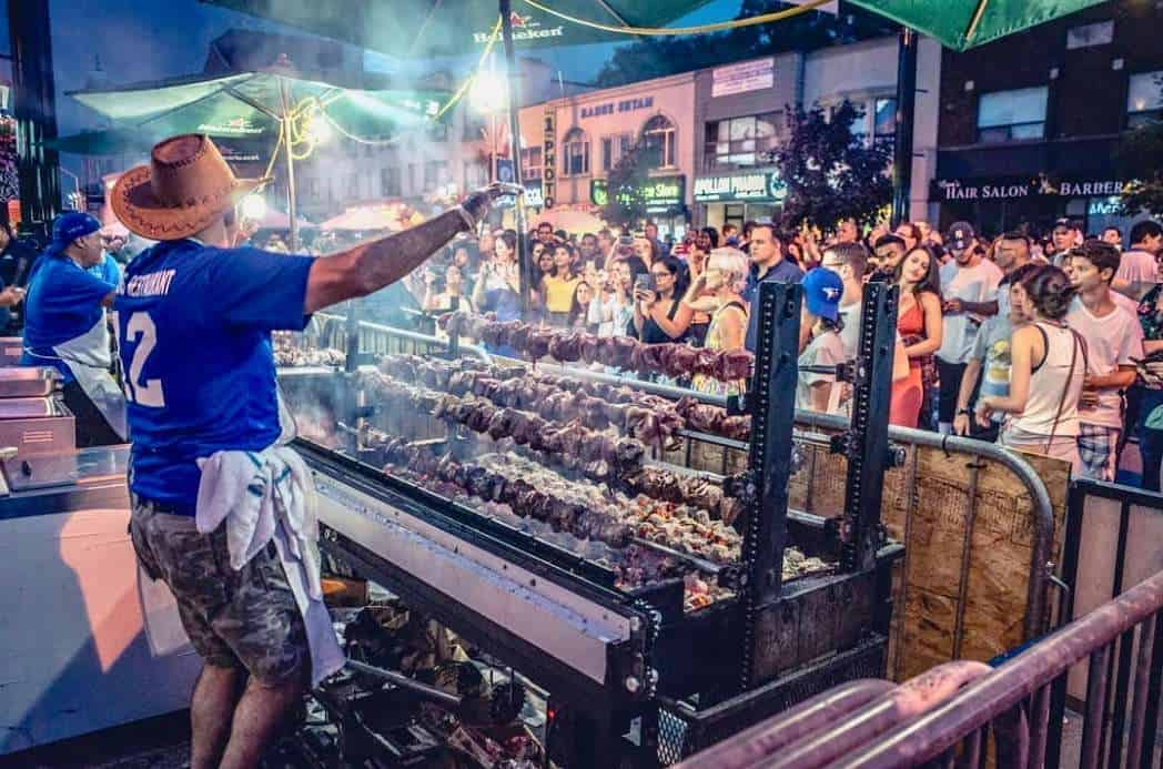 Meat being cook on a large grill at Tastes of the Danforth