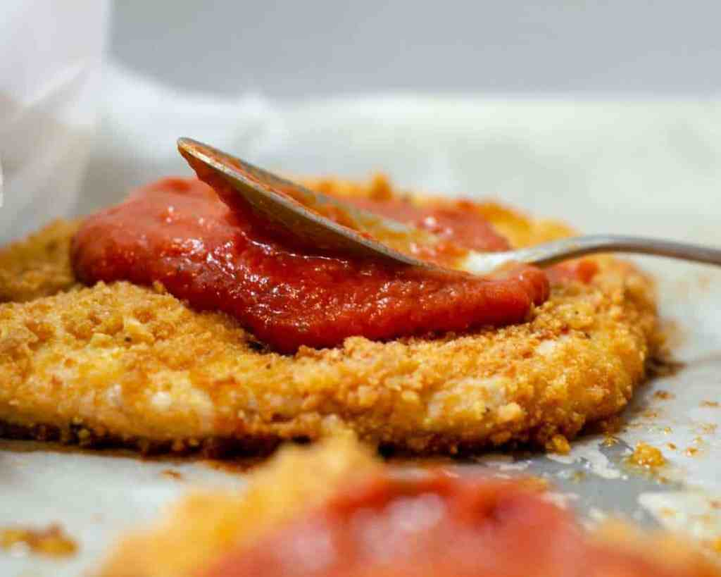 Crispy baked pork rind breaded chicken being topped with marinara