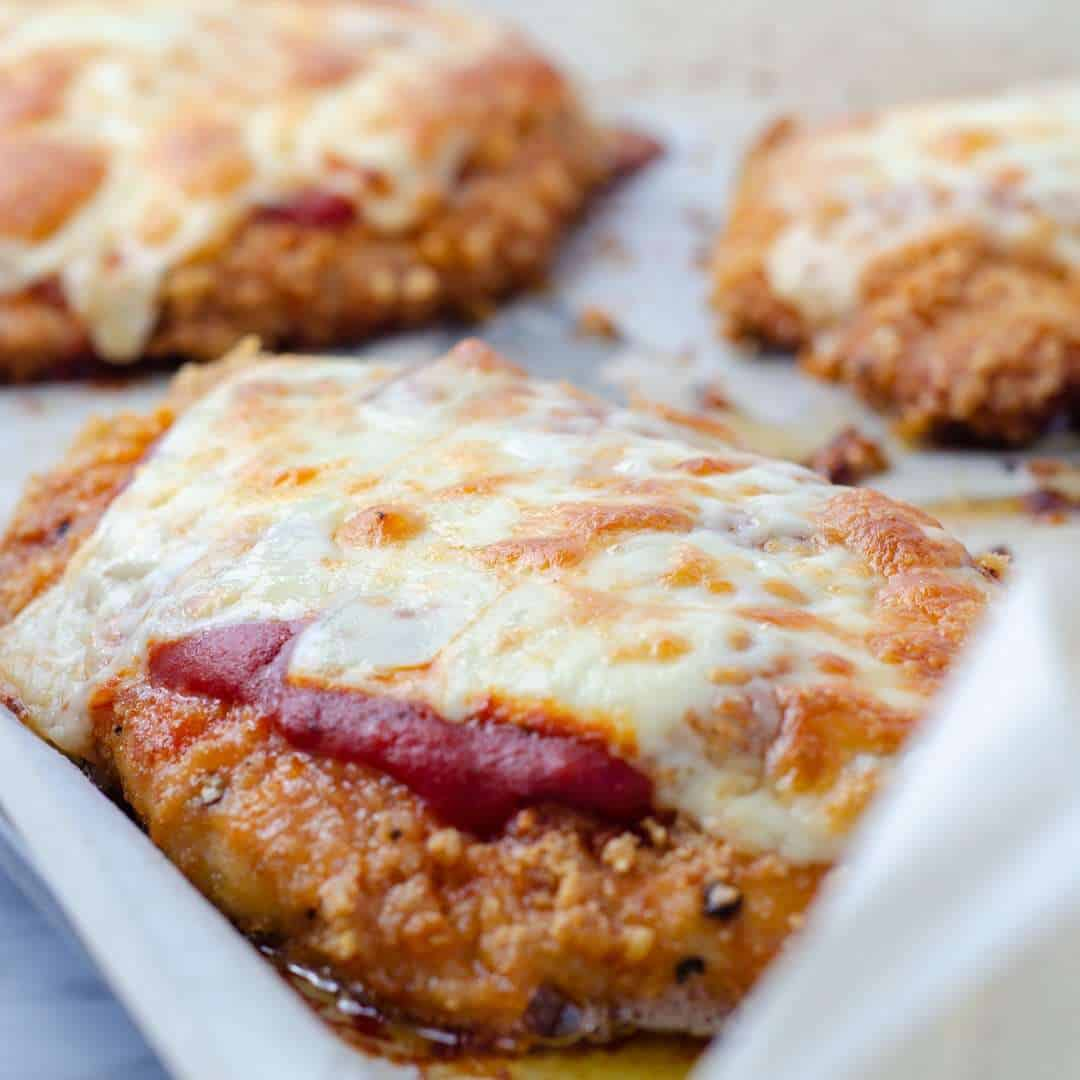 Keto chicken parmesan with melted cheese on a baking sheet