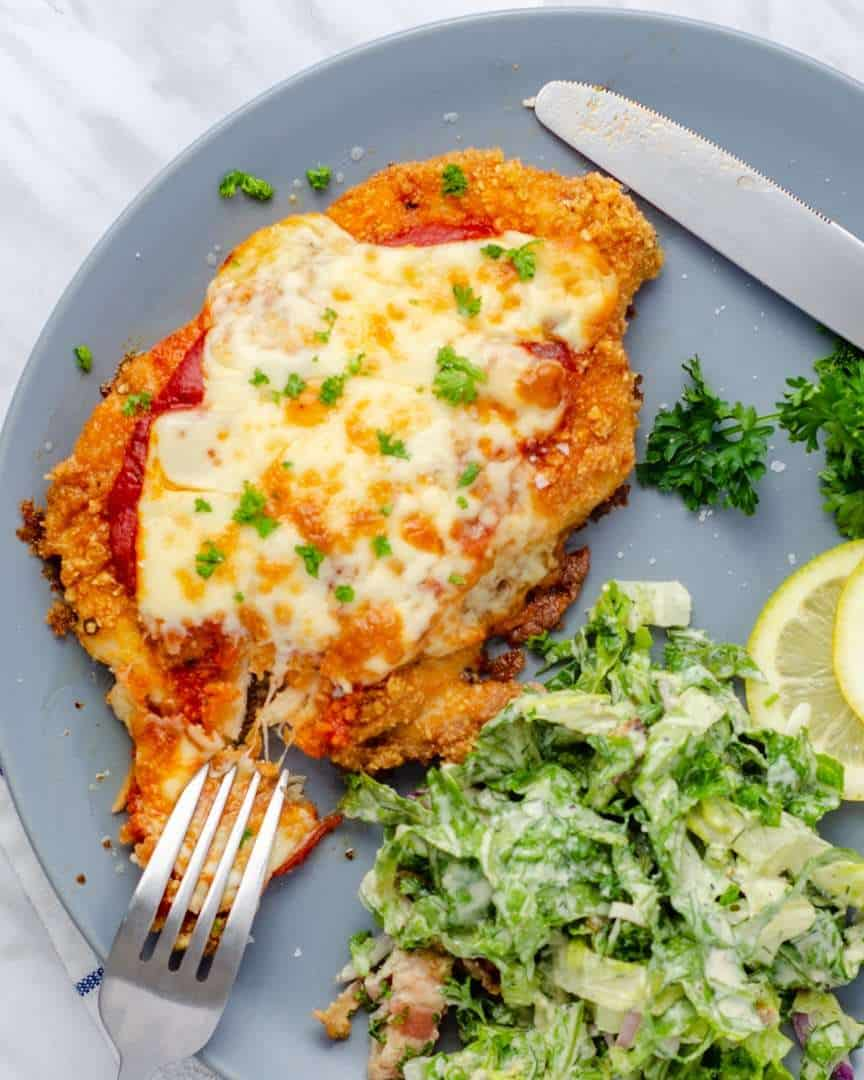 Keto Chicken Parmesan with Caesar salad on a plate