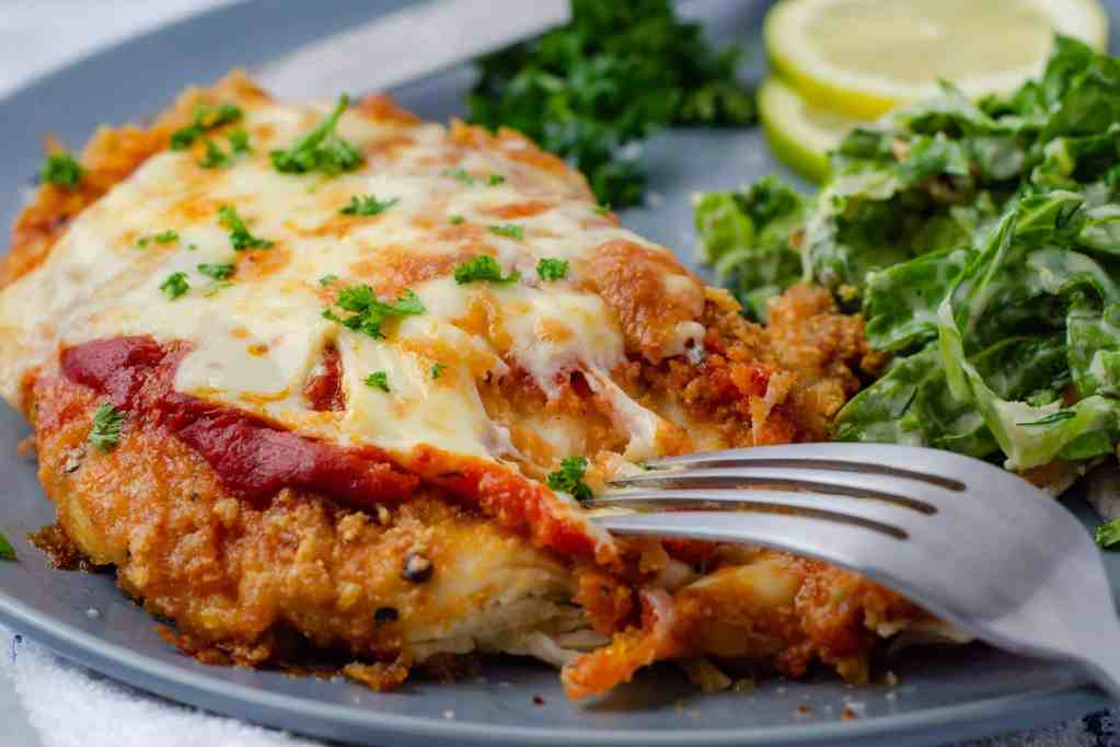 Keto Chicken Parmesan with melty cheese on a grey plate