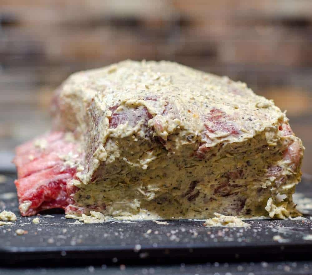Pork ribeye roast raw, slathered in a herb filled butter