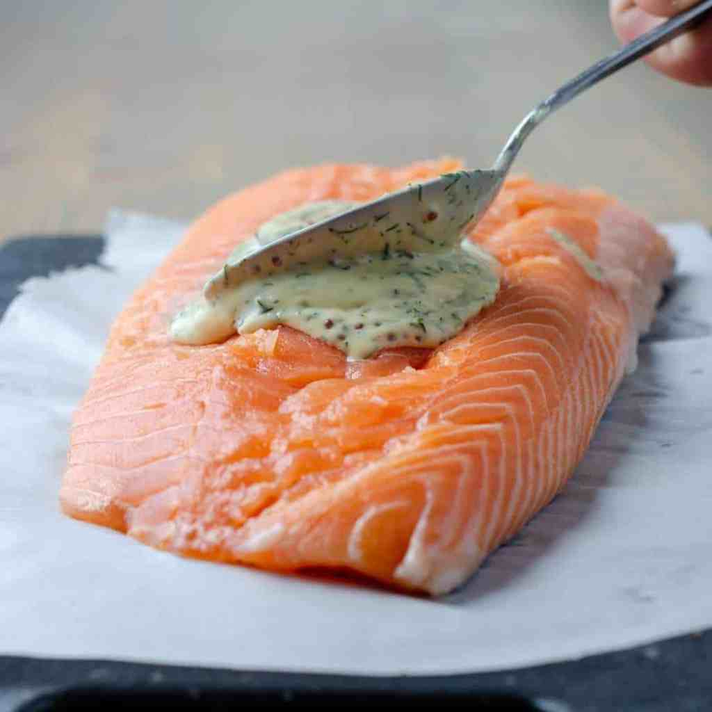 Raw salmon with honey dijon mayo being spread over top