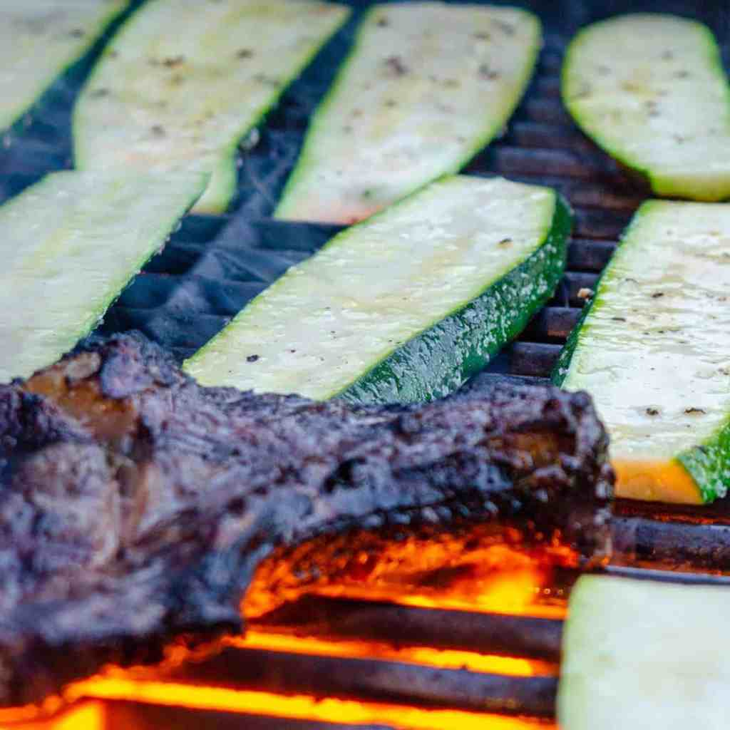 Slabs of zucchini on a grill with steak
