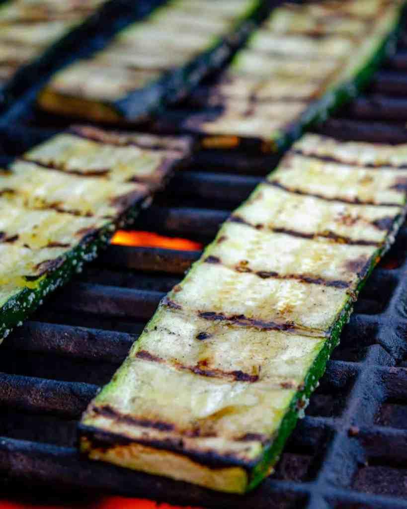 sSlabs of fresh cut zucchini on a BBQ