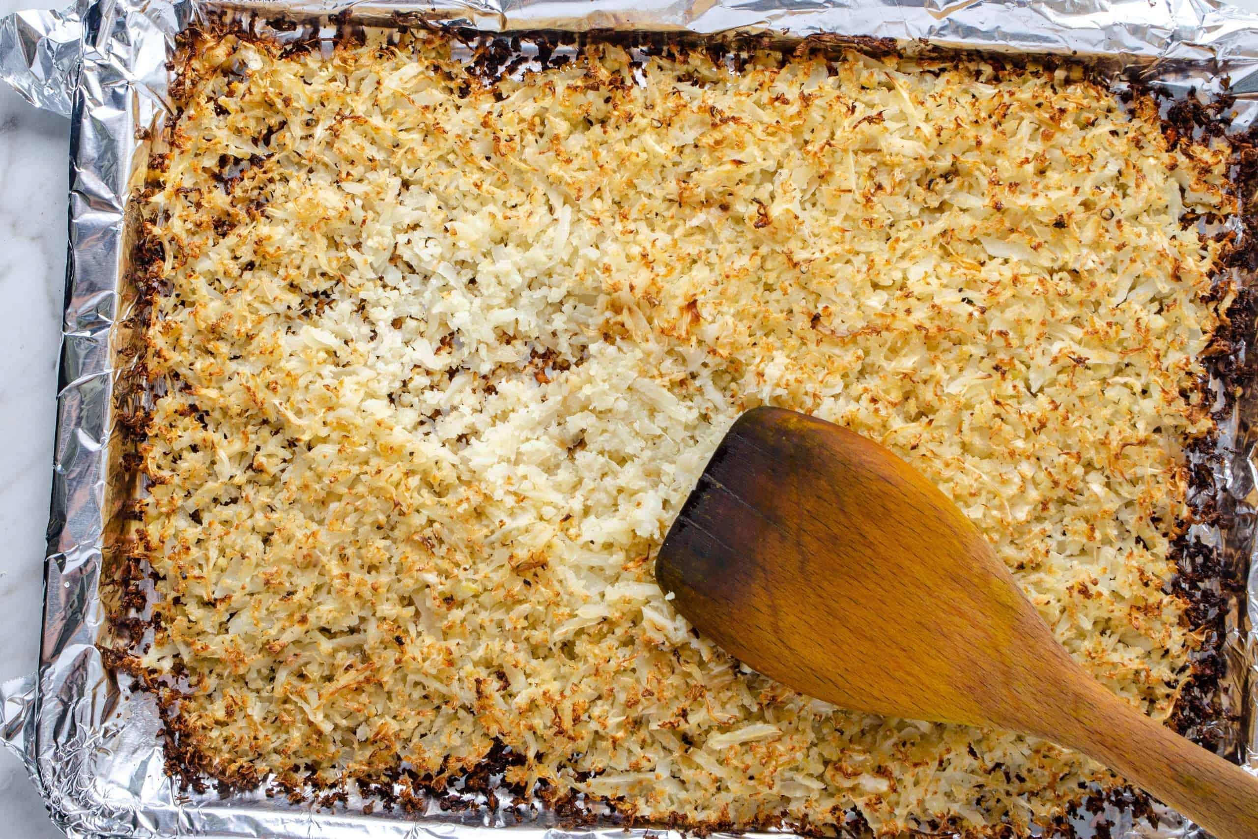 Roasted cauliflower rice on a baking sheet