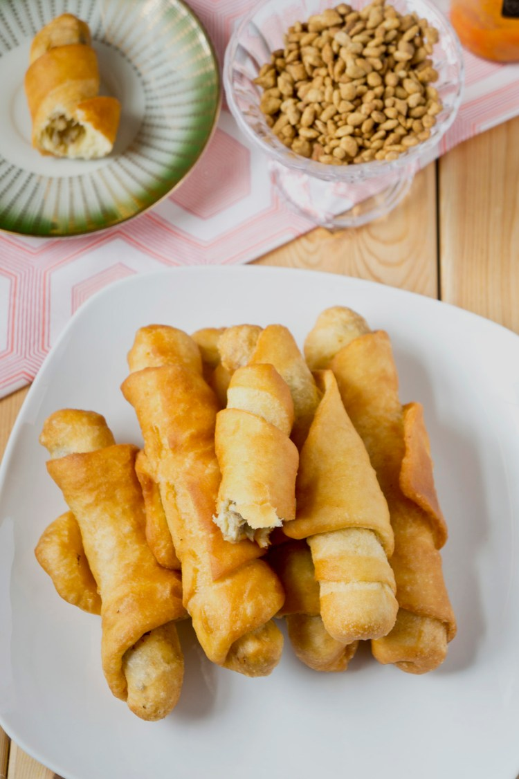 A stack of cameroon fish rolls on a plate, a half eaten roll on another plate and some groundnuts in a bowl