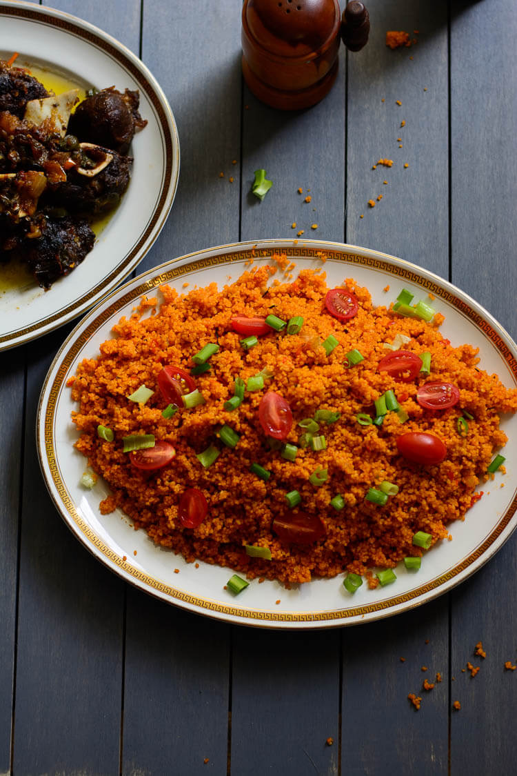 Jollof Couscous in 20 Minutes! - top view of Jollof couscous garnished with grape tomatoes and green onions and goat meat on the side