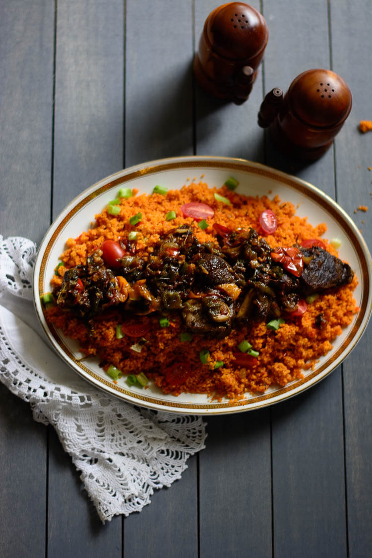 Jollof Couscous in 20 Minutes! - Jollof couscous garnished with grape tomatoes and green onions and goat meat on the top