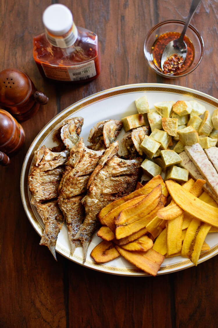 perch, fried Nigerian style with variety of chips served on table