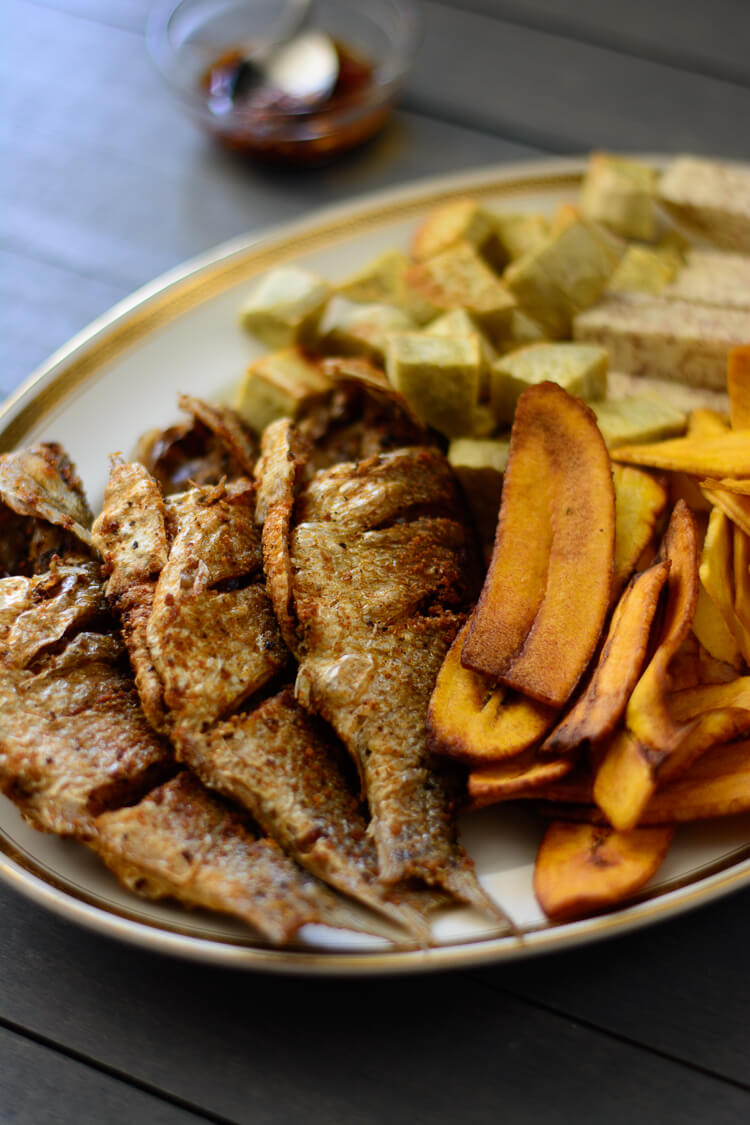 Nigerian fried fish on plate with chips on side