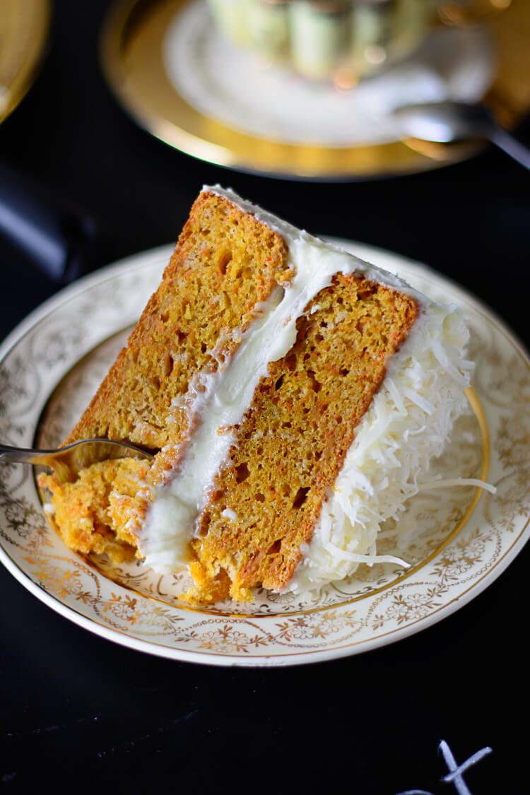 Cutting a piece of spiced carrot cake on a plate with a teaspoon