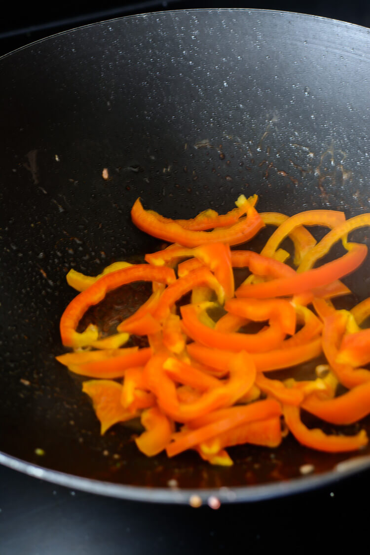 sauteing the red bell peppers in wok
