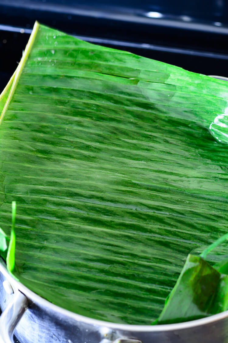 second layer of banana leaves covering moin moin in ramekins