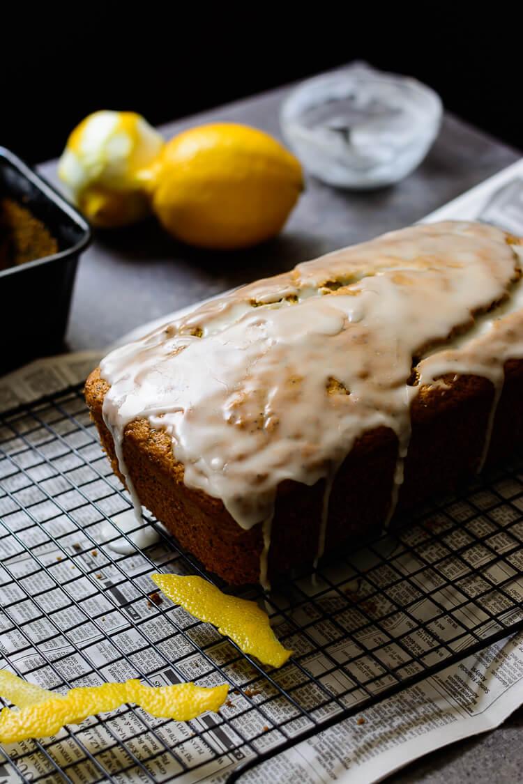vegan lemon poppy seed loaf cake - loaf on grill with lemon glaze spilling over