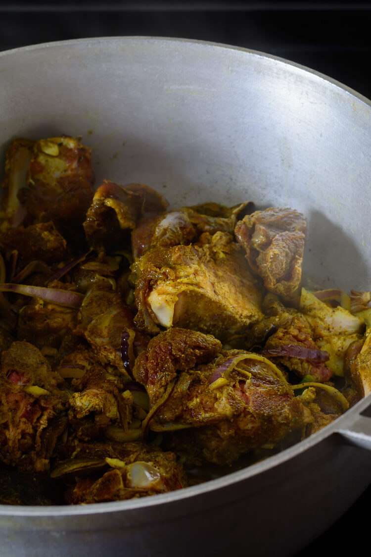 goat meat and curry powder added to pot