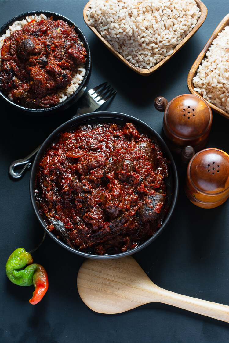 How to Make Ofada Stew (Nigerian Ofada Sauce Recipe) - top view of two dished bowls of ofada rice and stew with two wooden bowls of ofada rice on the side