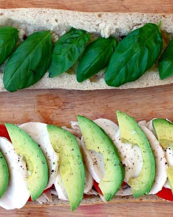 A Caprese sandwich on baguette with avocado, tomato, mozzarella, and basil.