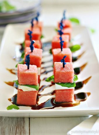 Cubes of watermelon are skewered with feta cheese and fresh basil and drizzled with balsamic.